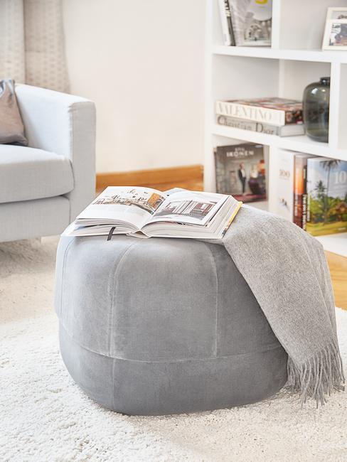 Poef in grijs met koffietafelboek in woonkamer