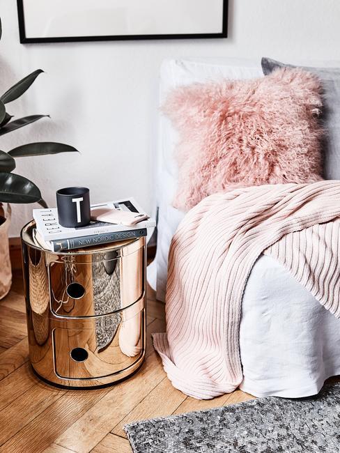 kleine woonkamer inrichten: zachte sierkussen in roze op plaid