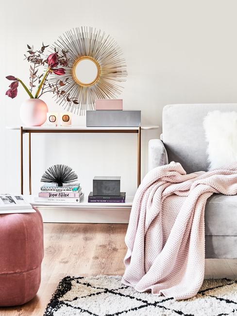 Woonkamer meubels: sidetable met decoraties, kaarsen, vaas met bloemen en wandspiegel