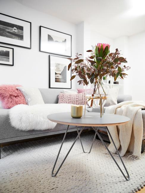Woonkamer meubels: salontafel met glazen vaas met bloemen op zacht vloerkleed