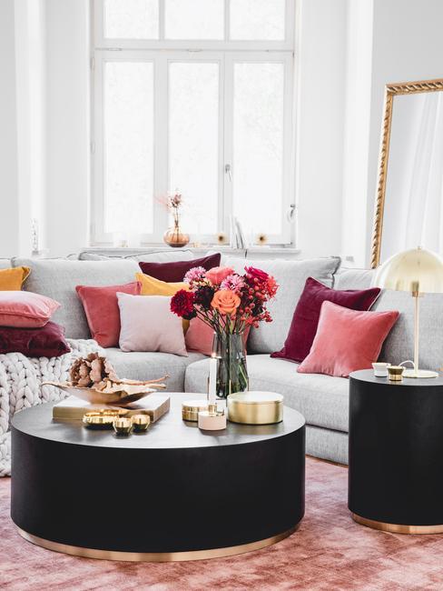 woonkamer kleuren: grijze zitbank met kleurrijke sierkussens en salontafel in zwart