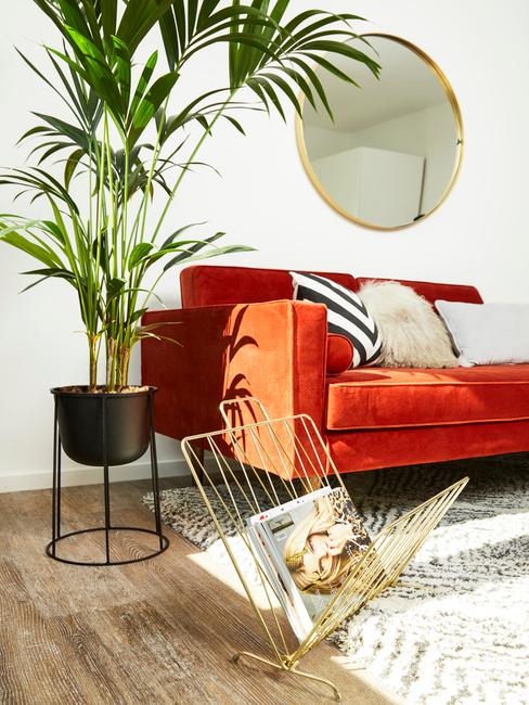 Woonkamer kleuren: oranje zitbank met sierkussens naast plantenpot en tijdschriftenhouder