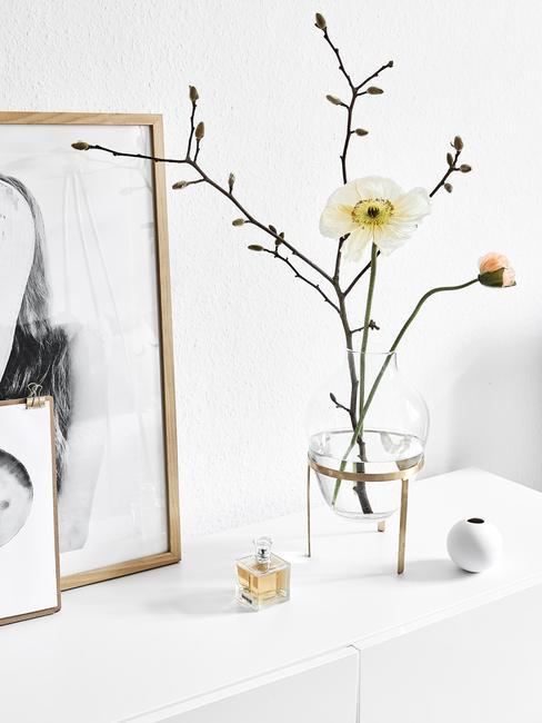 Transparant glazen vaas met takken en ingelijste print