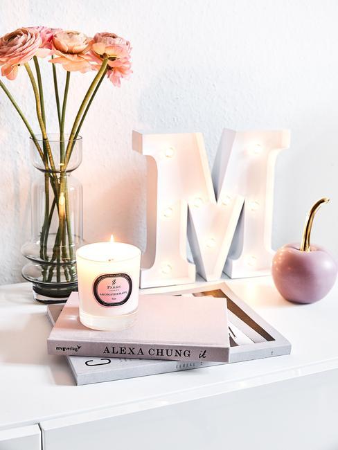 Decoraties op sideboard in wit: geurkaarsen, dienbladen, koffietafelboek