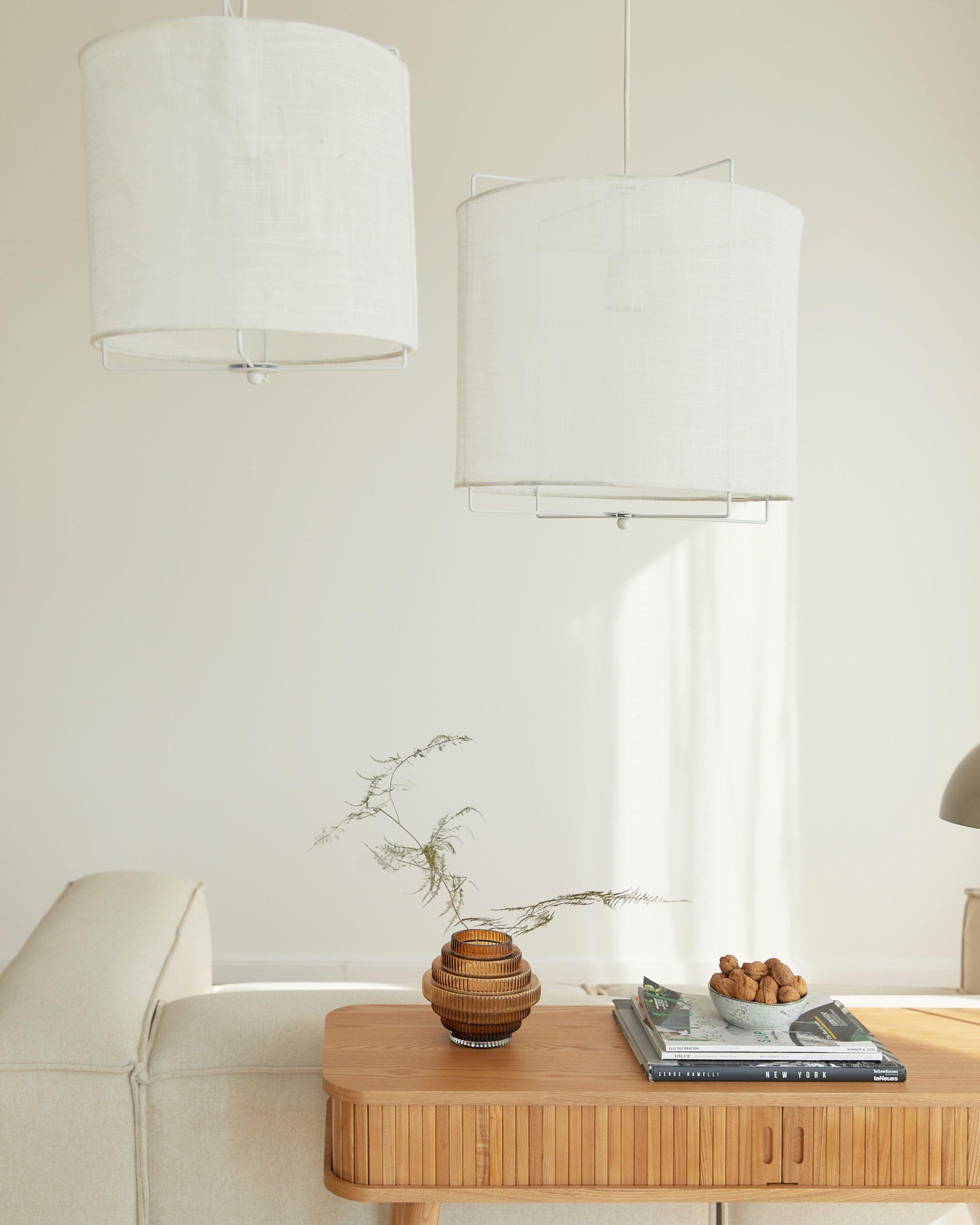 Lichte woonkamer met twee ronde hanglampen en witt lennon sofa