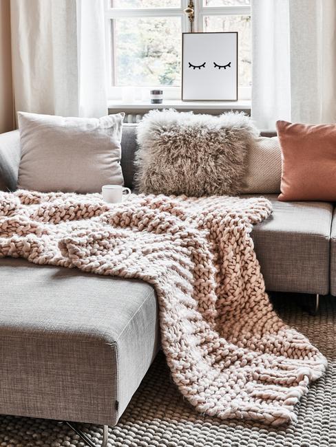 Zachte plaid in grijs op comfortabele zitbank met sierkussens en schapenvachr