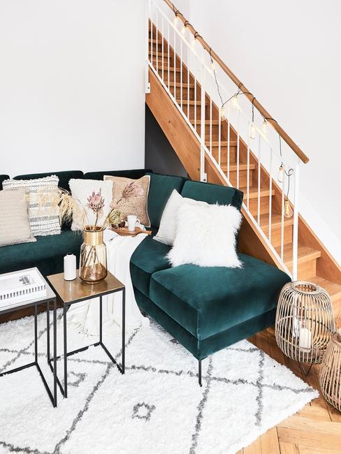 Fluwelen zitbank in groen met sierkussens in wit op vloerkleed