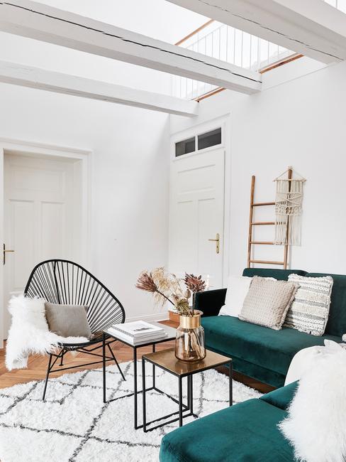 woonkamer groen: rotan fauteuil in zwart naast een fluwelen zitbank met sierkussens