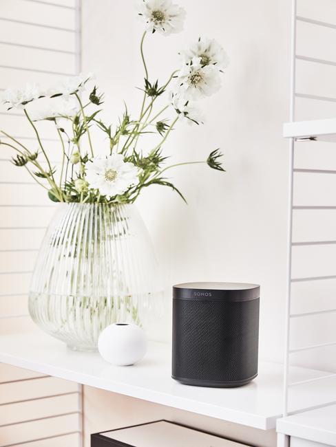 Transparante glazen vaas met bloemen naast zwarte opbergdoos
