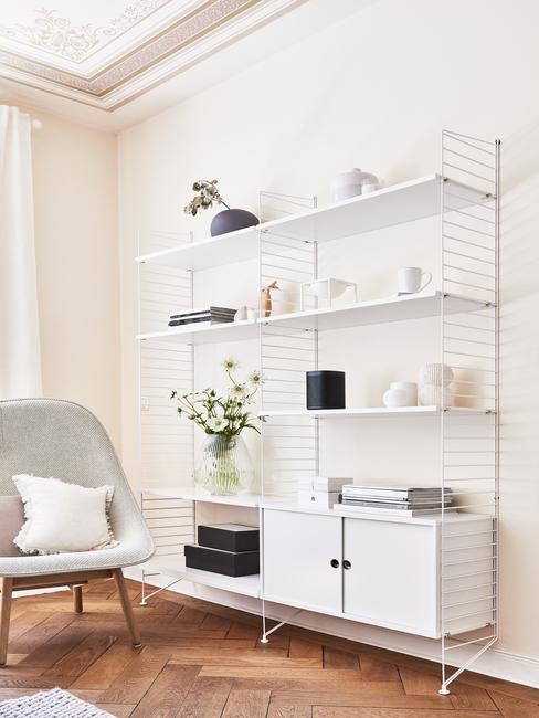 Wandrek in wit met decoraties en bloemen in vaas naast fluwelen fauteuil in grijs