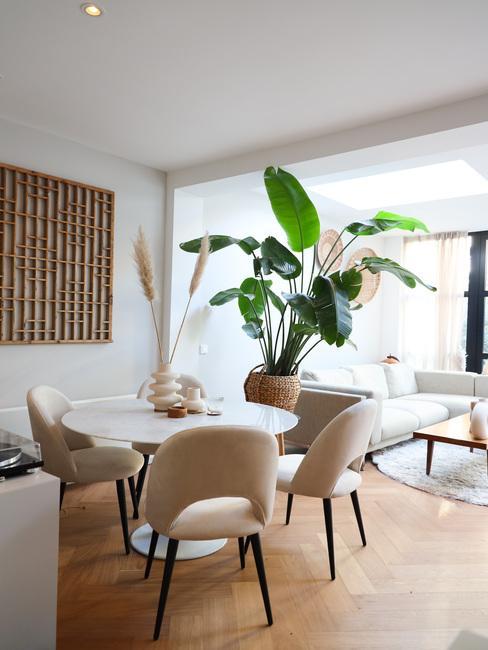 Ronde marmeren tafel in huiskamer met witte rachel eetkamerstoelen