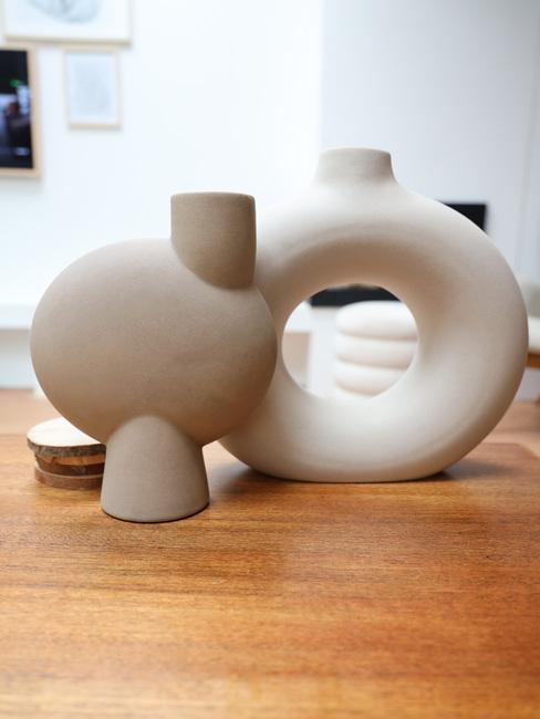 Witte handgemaakte ronde vazen op houten tafel