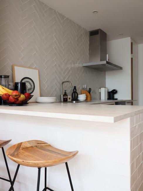 Keuken met witte tegels en houten barkrukken