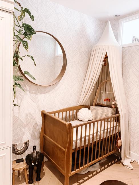 Kinderbed met witte klamboe en hangplant