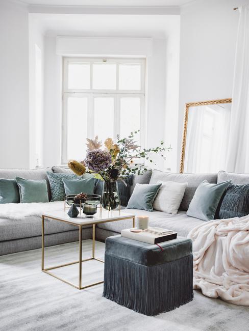 vensterbank decoratie: comfortabele zitbank met sierkussens en salontafel in goud kleur