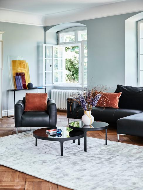Woonkamer in wit met zwarte leren zitbank en fauteuils
