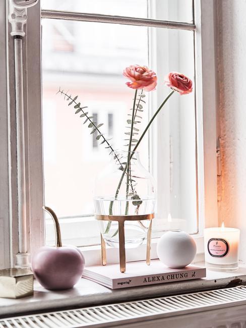 Vensterbank decoratie, bloemen in transparante glazen vaas, geurkaarsen
