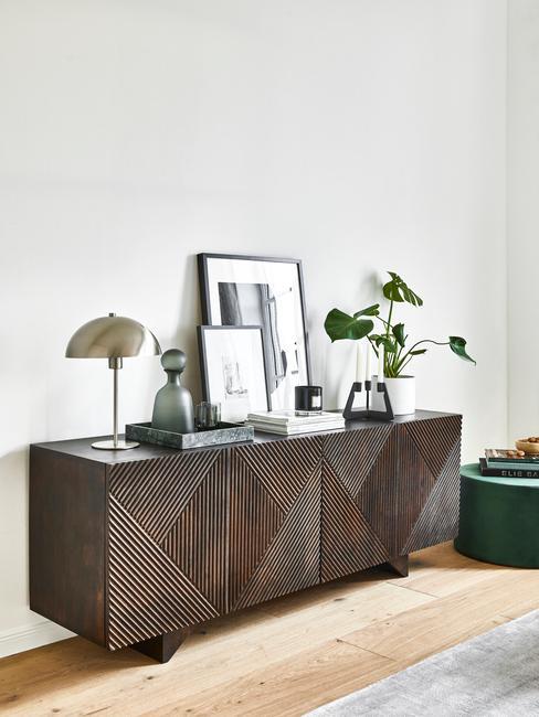donkerhouten dressoir met zilveren lamp en kamerplant