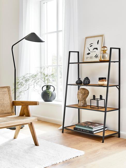 hoge zwarte lamp en rotan stoel met open wandkast