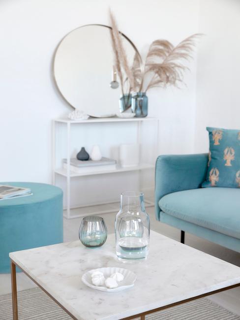 woonkamer met marmeren salontafel en blauwe bank