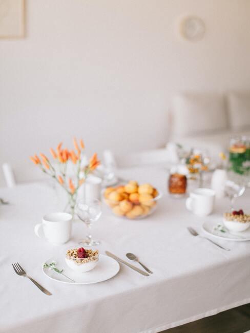 Wit tafellinnen met kunstbloemen en servies