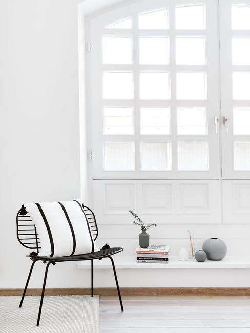 hoge openslaande deuren met raamdecoratie en zwarte stoel