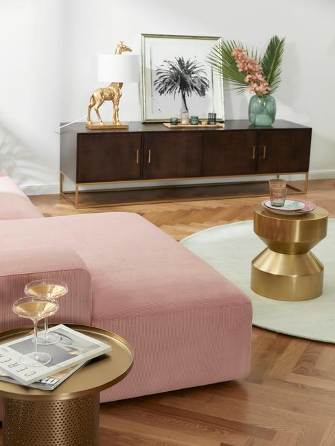 Grote woonkamer met roze marsmallow bank en gouden bijzettafel