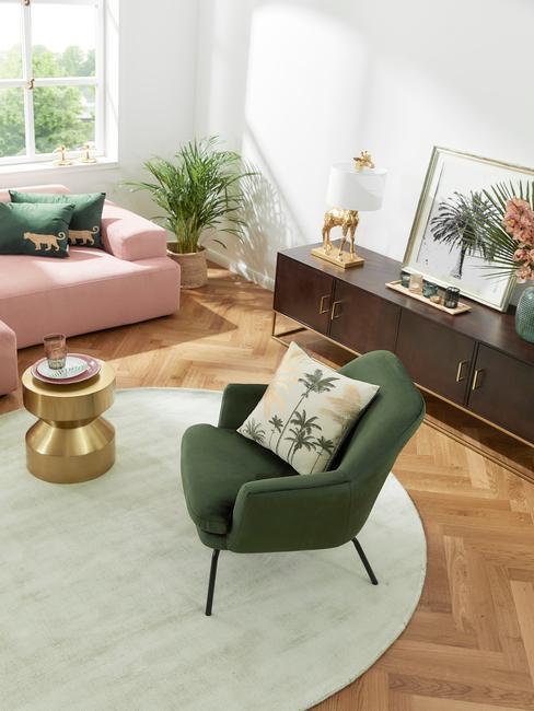grote woonkamer met groene feateuil wit rond vloerkleed en donkerhouten dressoir