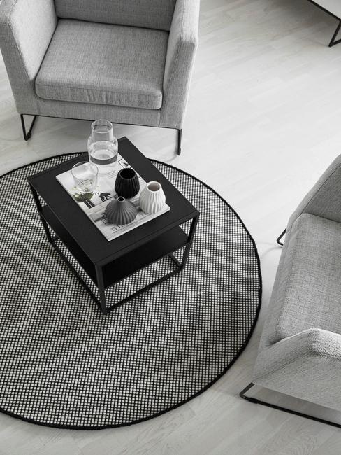 Grijs rond vloerkleed in woonkamer grijze armleunstoelen en zwarte bijzettafel