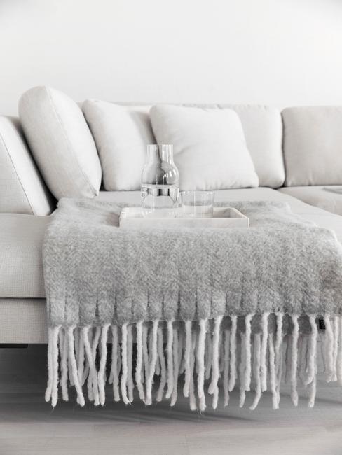 witte bank in woonkamer met grijze plaid