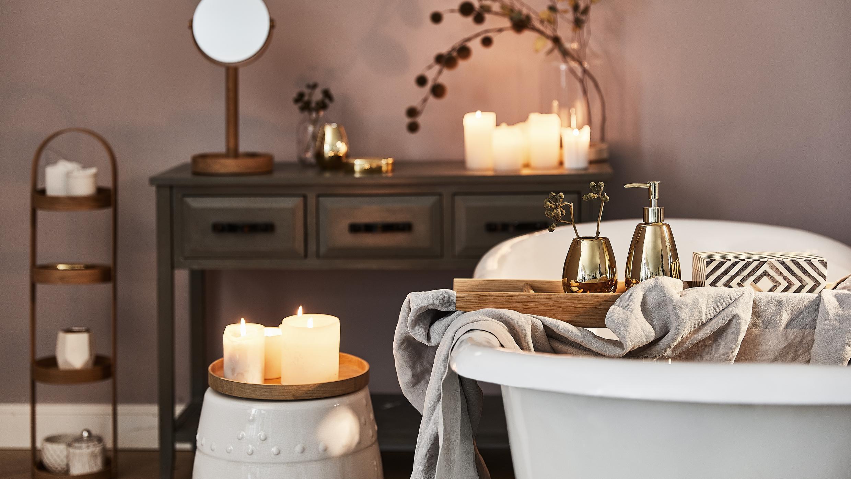Persoonlijke verzorging badkamer met bad, bijzettafel, bruine wandtafel en veel kaarsen, handdoeken en make-up spiegel