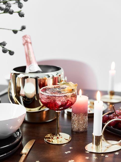 champagne fles in koeler met cocktail en roze kaarsen