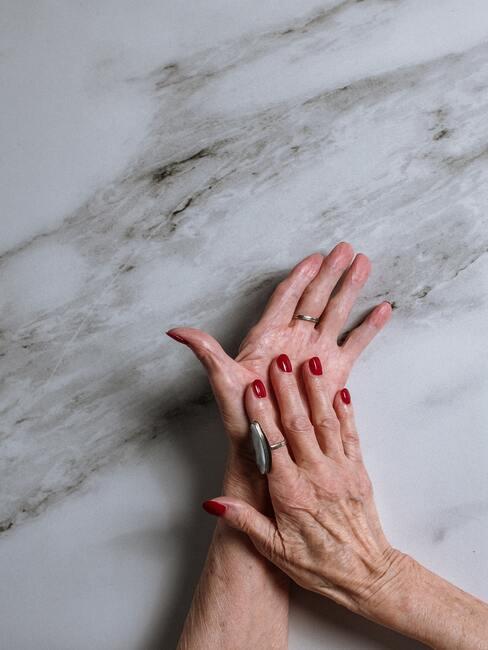 Rode nagels op de achtergrond van een marmeren blad