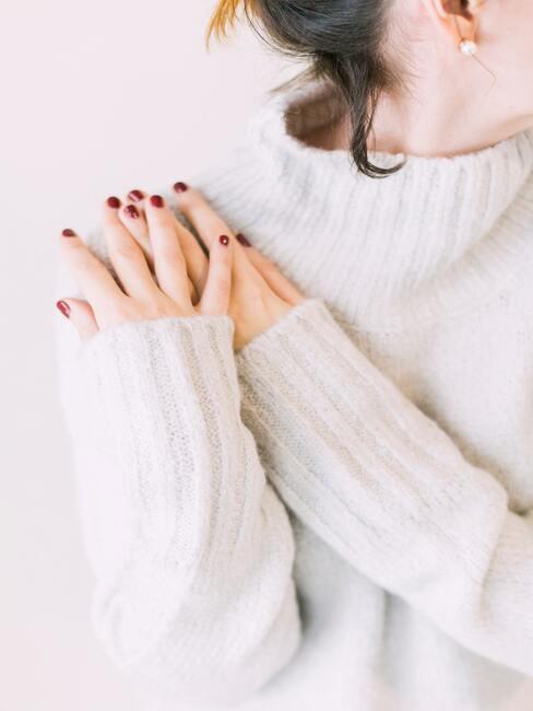 Een vrouw in een beige trui met rode nagels