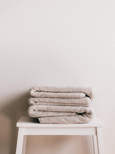 Handdoeken in beige en grijs op witte sideboard