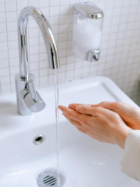 vette huidvrouw haar handen wassen in de badkamer