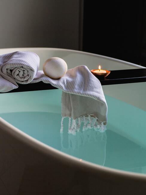 badkuip vol water met een handdoek