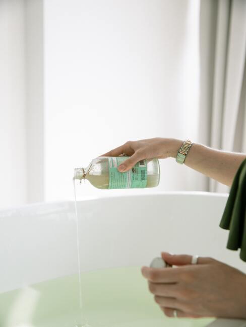 vrouw giet bubbelbad in de badkuip