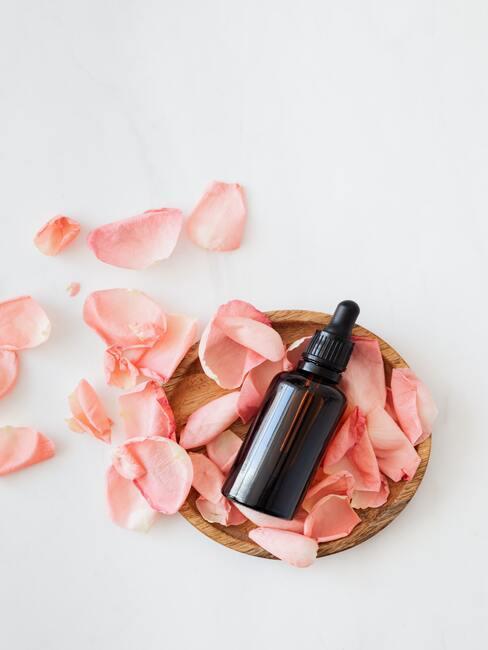 Castor olie met rozenblaadjes op een decoratief dienblad