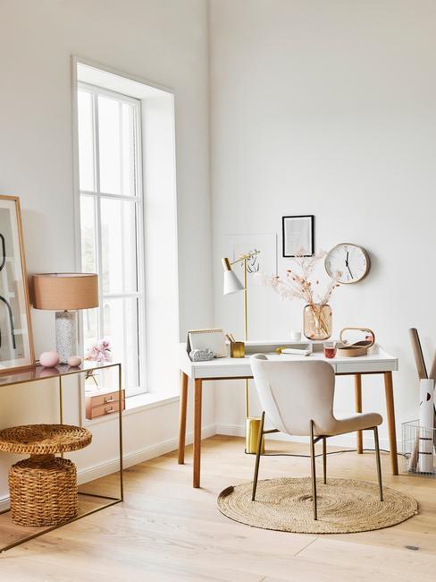 Wit bureau met een beige stoel en rieten kleed