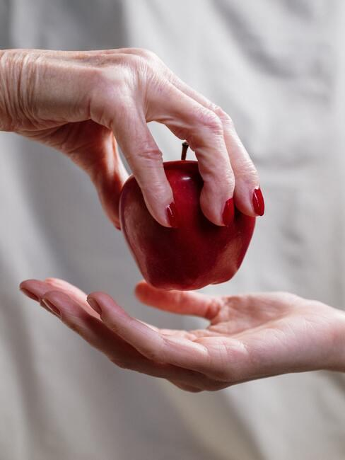 Rode appel met hand met sterke nagels