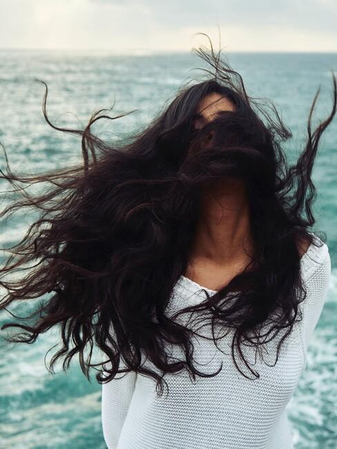 Vrouw met grote bos zwarte haren aan het uitwaaien op het strand