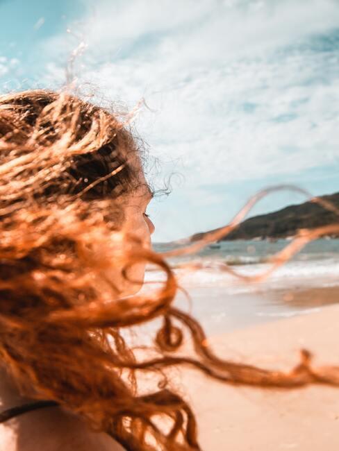 Vrouw met rood haar op het strand