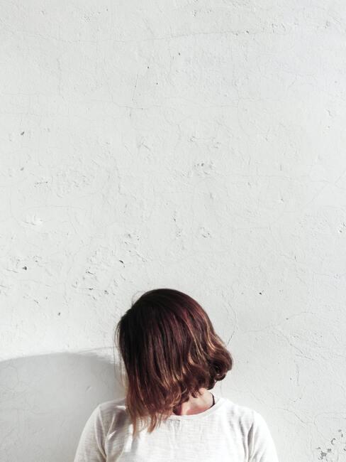 vrouw met kort haar voor een witte muur