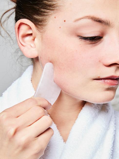 vrouw met gezichtssmassage steen van rooskwarts masseert haar gezicht