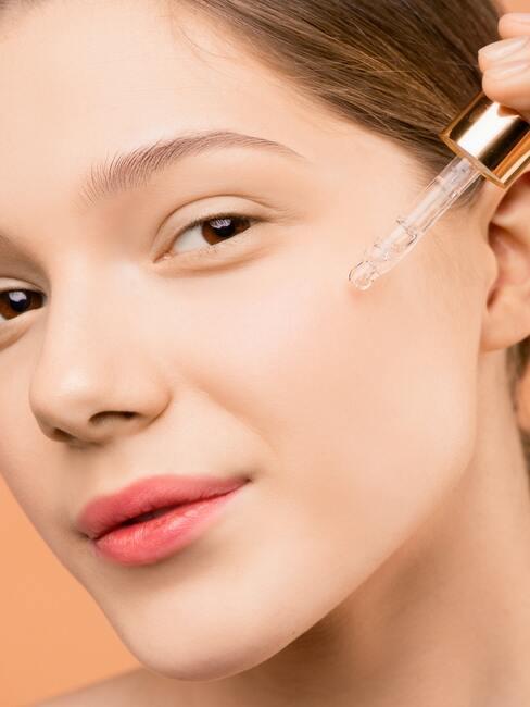 gezicht van vrouw die serum aanbrengt voor een vette huid