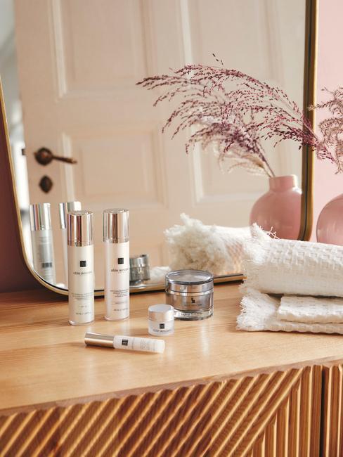 dressoir met grote spiegel en verschillende schoonheidsproducten