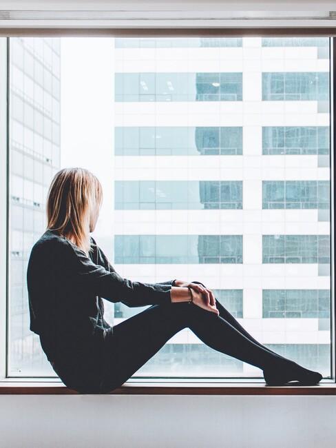 vrouw zit op vensterbank en staart uit het raam naar buiten