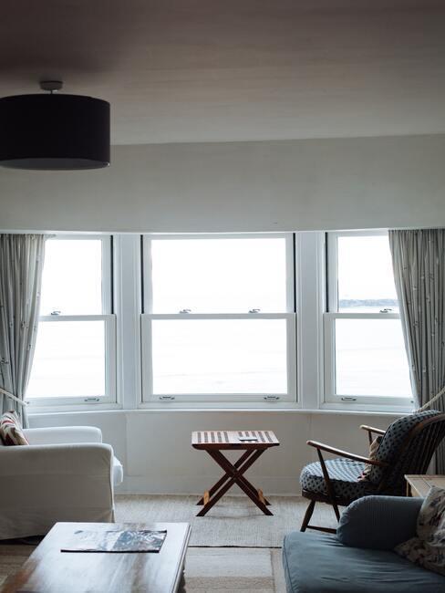 Grote woonkamer met breed raam en twee lounge stoelen