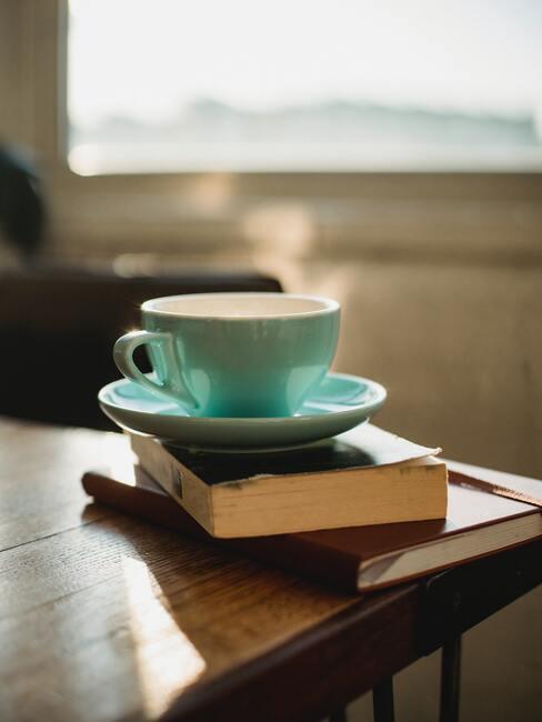 stapel met boeken en een kop koffie bovenop